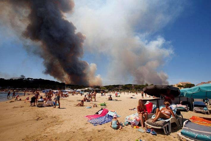 Smoke fills the sky above a burning hillside as tourists relax on the beach in Bormes-les-Mimosas