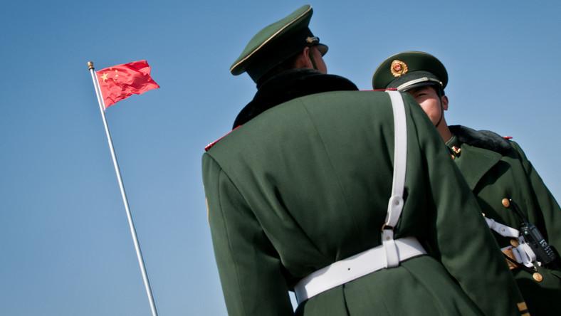 Chińscy żołnierze przed flagą na placu Tiananmen w Pekinie