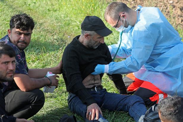 Ratownik pogotowia ratunkowego i członkowie grupy uchodźców odnalezionych na granicy polsko-białoruskiej w pobliżu miejscowości Usnarz Górny
