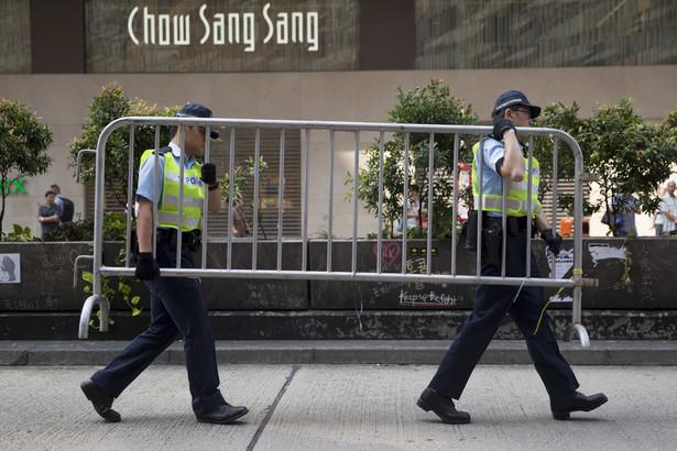 Protesty w Hongkongu. Policjanci przenoszą barykady obok sklepu jubilerskiego Chow Sang Sang Holdings International Ltd. na Nathan Road w dzielnicy Mong Kok w Hong Kongu.