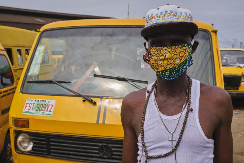 A bus conductor in Lagos complies with the face mask directive the right way (Pulse)