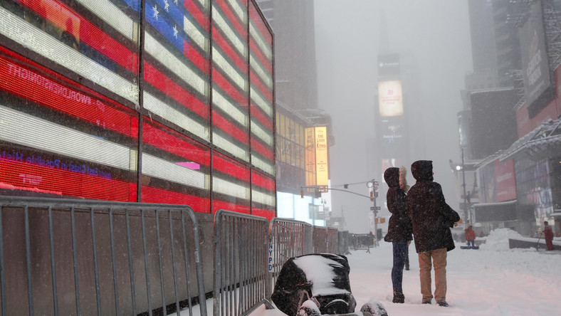 People stand during a snowstorm at Times Square in the Manhattan borough of  New York