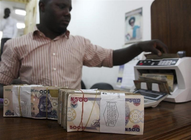 A money dealer counts the Nigerian naira on a machine in his office in the commercial capital of Lagos, in a file photo. REUTERS/Akintunde Akinleye