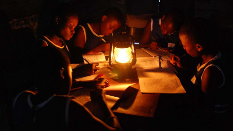 Image of student reading with lantern (file photo)