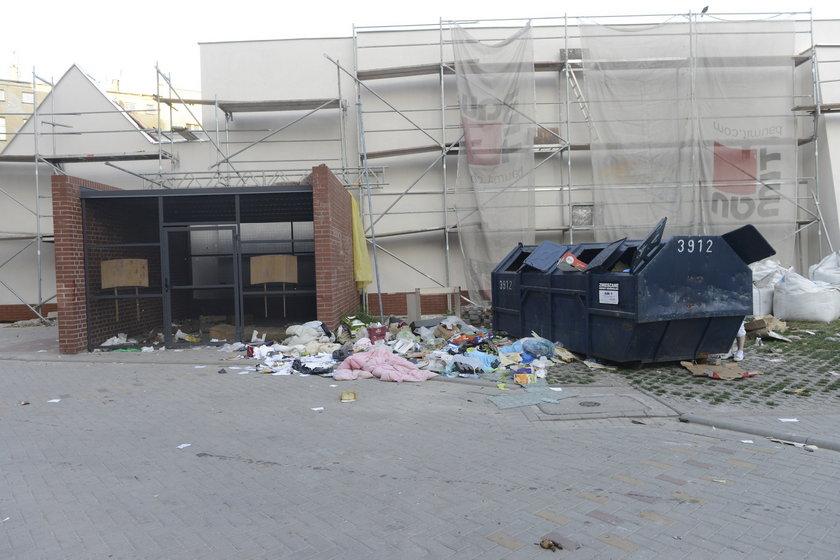 Osłonka śmietnikowa, a obok niej kontener na śmieci