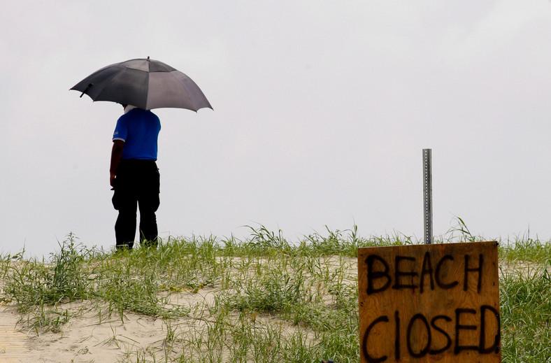 Katastrofa w Zatoce Meksykańskiej: Grand Isle, Louisiana, USA. Człowiek z parasolem na zamknięctej plaży przygląda się zniszczeniom jakich dokonała ropa. Foto: Derick E. Hingle/Bloomberg