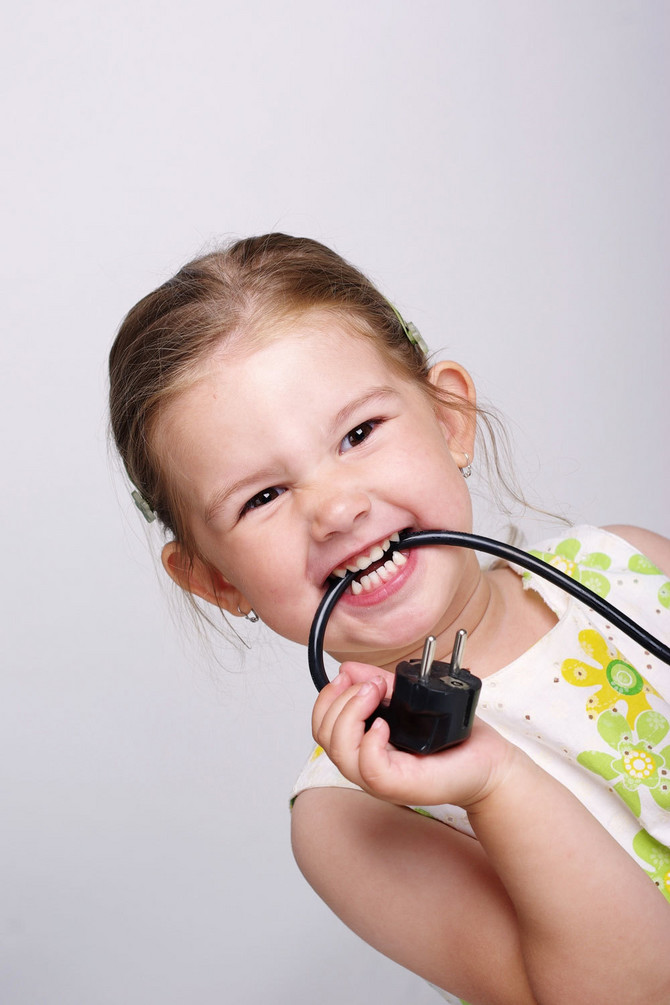 3773_web-devojcica-grize-kabl-stock-photo-a-small-child-with-a-dangerous-black-electric-cable-shutterstock_34750438