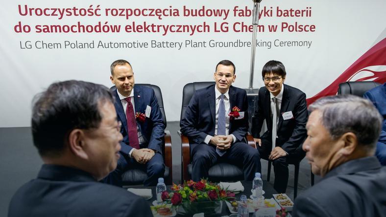 Wicepremier, minister finansów i rozwoju Mateusz Morawiecki (C), wojewoda dolnośląski Paweł Hreniak (L) oraz tłumacz Joo-Hyun Nam (P) podczas uroczystości rozpoczęcia budowy fabryki baterii do samochodów elektrycznych LG Chem Energy