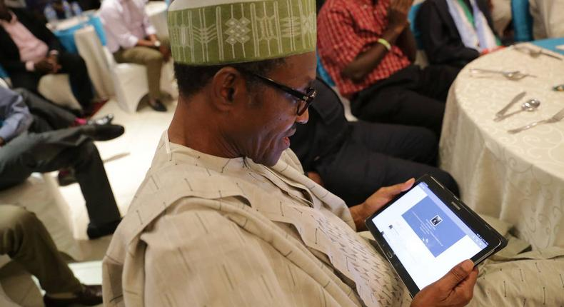 President Muhammadu Buhari checking out his twitter page on a Tablet during a meeting with campaign volunteers in Lagos in 2014. (Sahara Reporters)