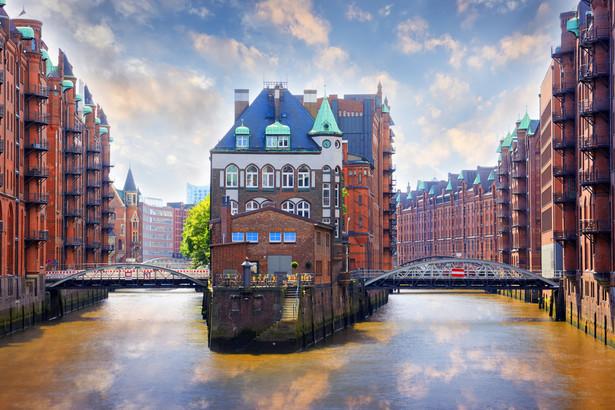 HamburgHamburg to nie tylko jeden ze słynniejszych europejskich portów. Jeśli lubisz w miastach dzielnice fabryczne, a jeszcze lepiej starych magazynów, na pierwszy ogień zwiedzania weź dzielnicę spichlerzy, czyli Speicherstadt. Neogotycka zabudowa tej części Hamburga położona nad kanałami zachwyci każdego miłośnika weneckich klimatów. W części budynków nadal przechowuje się towar, pozostałe służą jako muzea lub powierzchnie wystawowe. Mieści się tam muzeum Miniatur Wunderland. To kolej w wersji mini, ale imponująca rozmachem. Liczy ponad 10 000 wagonów i 4 110 budowli i mostów. Przy okazji możesz podejrzeć, jak idzie tworzenie pobliskiej futurystycznej dzielnicy Hafen City, do której przynależy dziesięć obszarów przeznaczonych na konkretne dziedziny, aktywności np. naukę, rozrywkę/handel itp. Na pewno nie przegapisz Elbphilharmonie. Dlaczego? Jak przystało na miasto, którego historia i tradycja jest związana z wodą, budynek filharmonii też przypomina rozgniewane fale. W październiku spróbuj tutejszego przysmaku Fliederbeersuppe, czyli zupy na bazie czarnego bzu (dokładniej soku z jego owoców). Dodawane są tu jeszcze kluski, czasem jesienne owoce np. jabłka. Wolisz coś bardziej treściwego? Sięgnij po kiełbaskę curry, czyli po prostu w sosie pomidorowym okraszonym tą przyprawą.