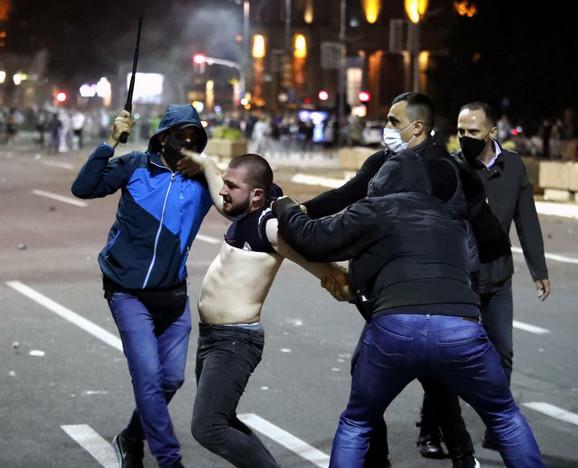 Sa kapuljačom na glavi, maskom i naočarima za sunce, policajac u civilu udara demonstranta