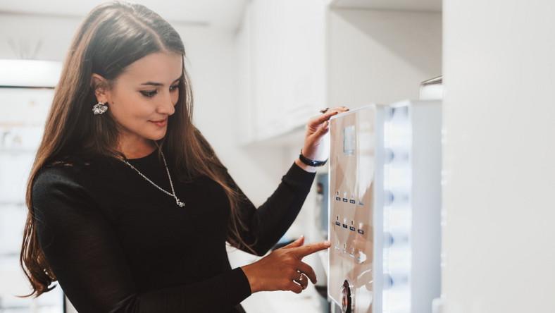 Kobieta zamawia kawę. Automat do kawy