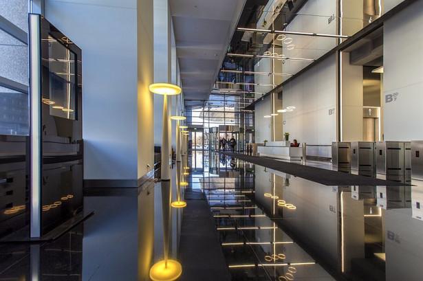 Potrzebę aranżacji biura w sposób zgodny z oczekiwaniami najemców doskonale rozumieją właściciele położonego w samym sercu stolicy, przy ulicy Emilii Plater, biurowca Warsaw Financial Center – Tristan Capital Partners. Dziś na 32 piętrach tego budynku swoje siedziby i oddziały mają najbardziej liczące się w kraju i zagranicą firmy, m.in. z branży finansowej, doradczej i nowych technologii. Stale podnosząc standardy użytkowania, WFC implementuje najnowsze rozwiązania technologiczne. Przejście przez bramki wejściowe z możliwością pominięcia recepcji ułatwia system QR kodów. Kod można pobrać tradycyjnie (w recepcji) lub otrzymać go mailem. W budynku działa inteligentny system wind – na panelu należy wystukać numer piętra, a system wskaże, do której windy należy się udać. Dzięki temu osoby jadące na te same piętra wsiądą razem, a winda zatrzyma się maksymalnie na pięciu piętrach. System skraca więc nie tylko czas oczekiwania, lecz również przemieszczania się pracowników. W zrewitalizowanym lobby uwagę zwraca imponująca ściana wizyjna, złożona z aż 24 55-calowych monitorów. To jedyna ogólnodostępna konstrukcja tego typu w Polsce. Można na niej prezentować dowolne treści wideo.