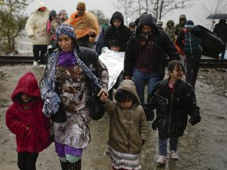 Migrants walk under rain after crossing the border from Greece into Macedonia, near Gevgelija