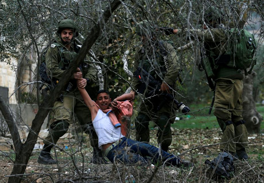 Israeli soldiers detain a Palestinian during clashes at a protest near the West Bank city of Nablus