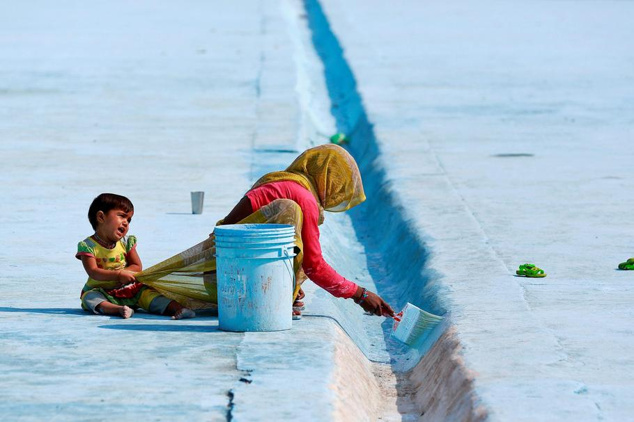 A woman paints the floor of a pond as her child pulls at her saree in Delhi