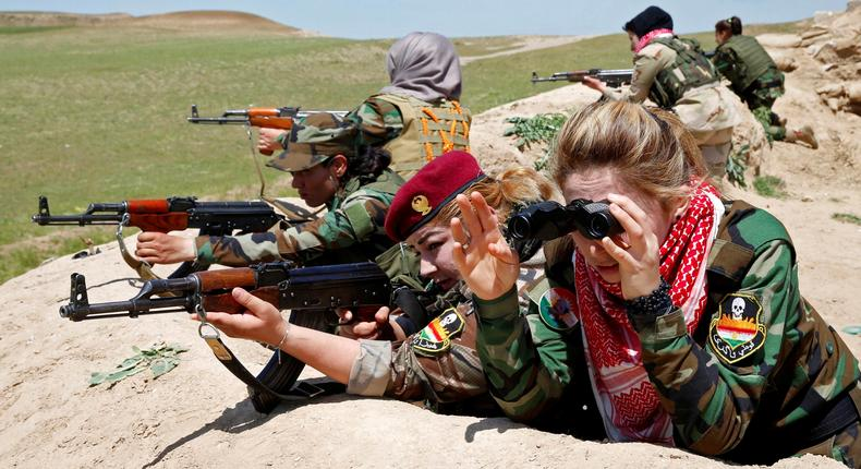 An Iraqi Kurdish female fighter and a Yazidi female fighter aim their weapons near the front line of the fight against ISIS near Mosul, Iraq, April 20, 2016.