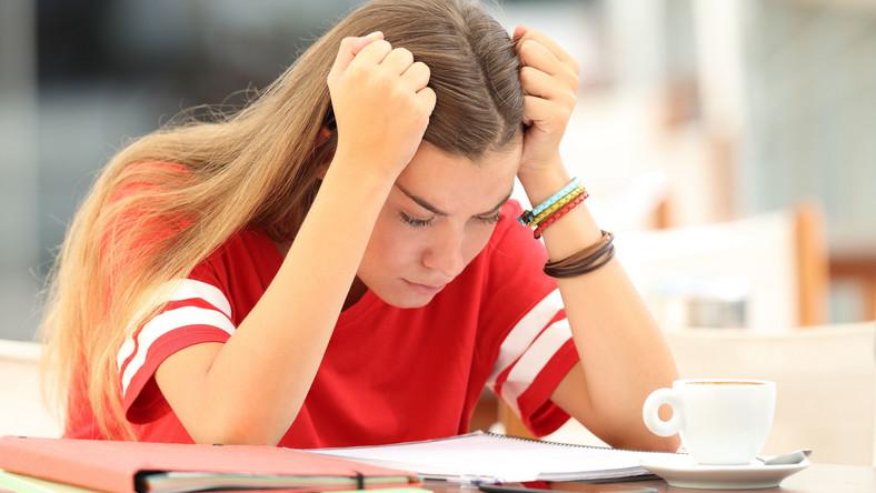 Nastolatka siedzi nad książkami