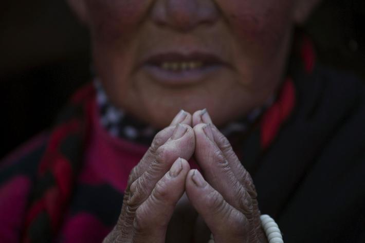 Woman prays as ethnic Tibetan people gather in sub zero temperatures on the hill above a Buddhist la