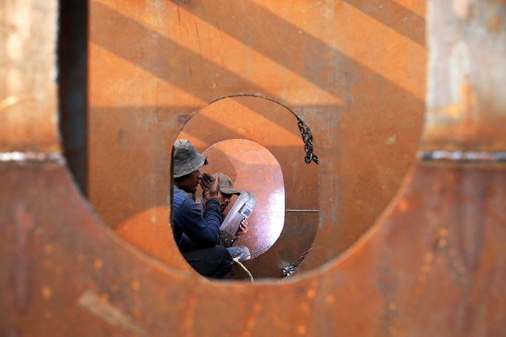 Workers weld iron sheets as they build a new ferry at a dockyard in Dhaka