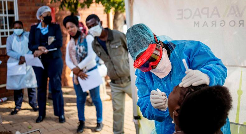 Doctors Without Borders nurse Bhelekazi Mdlalose performs a COVID-19 test on a health worker in Johannesburg, South Africa on May 13, 2020.