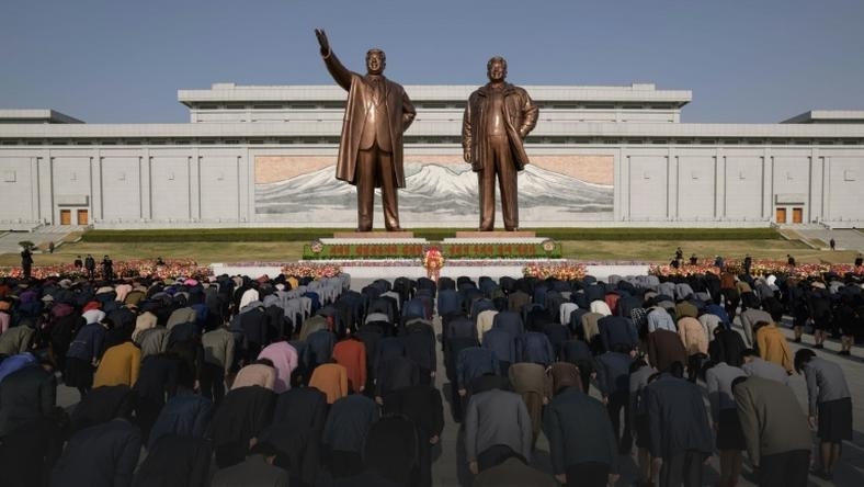 People pay their respects before the statues of late North Korean leaders Kim Il Sung and Kim Jong Il
