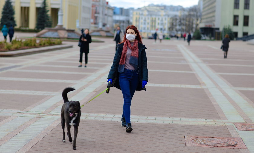 Young female using a face mask as a coronavirus spreading prevention walking with her dog. Global CO