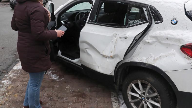 Uszkodzone BMW przy ul. Nowolipie w Warszawie. Przewożona koparka spadła z lawety na zaparkowane przy jezdni pojazdy.