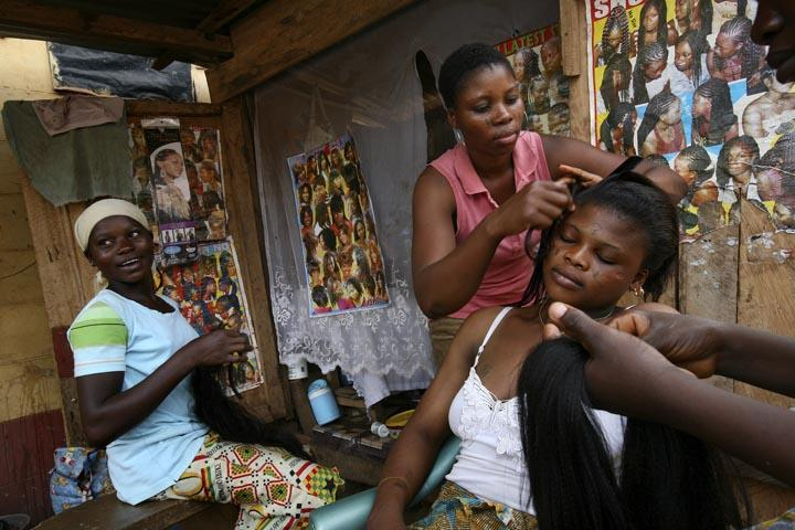 A hairdresser at a local salon busies herself with a client. - [Citi FM]