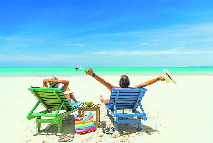 stock-photo-couple-relaxing-in-deck-chairs-on-the-tropical-beach-644081704