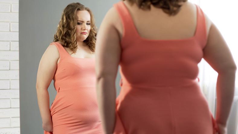 Otyła kobieta przegląda się w lustrze