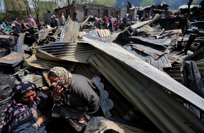 Women weep as they sit around remains of their houses gutted in a fire which broke out in a resident
