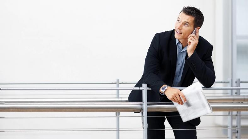 Businessman using mobile while leaning on a railing - Copyspace