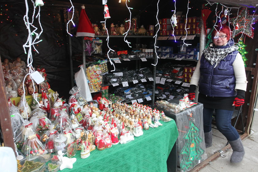 Sprzedaczyni stoi przy stoisku z świątecznymi ozdobami