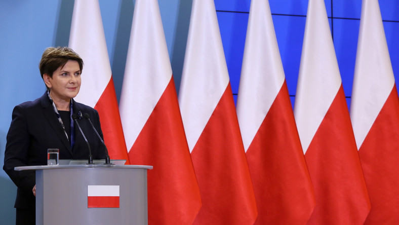 Premier Beata Szydło na tla biało-czerwonych flag