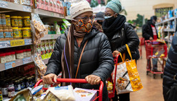 A woman wearing a mask moves her shopping cart inside a supermarket
