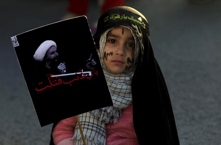 A Shiite Muslim girl holds a picture of Shiite Muslim cleric Nimr al-Nimr as she takes part in a p