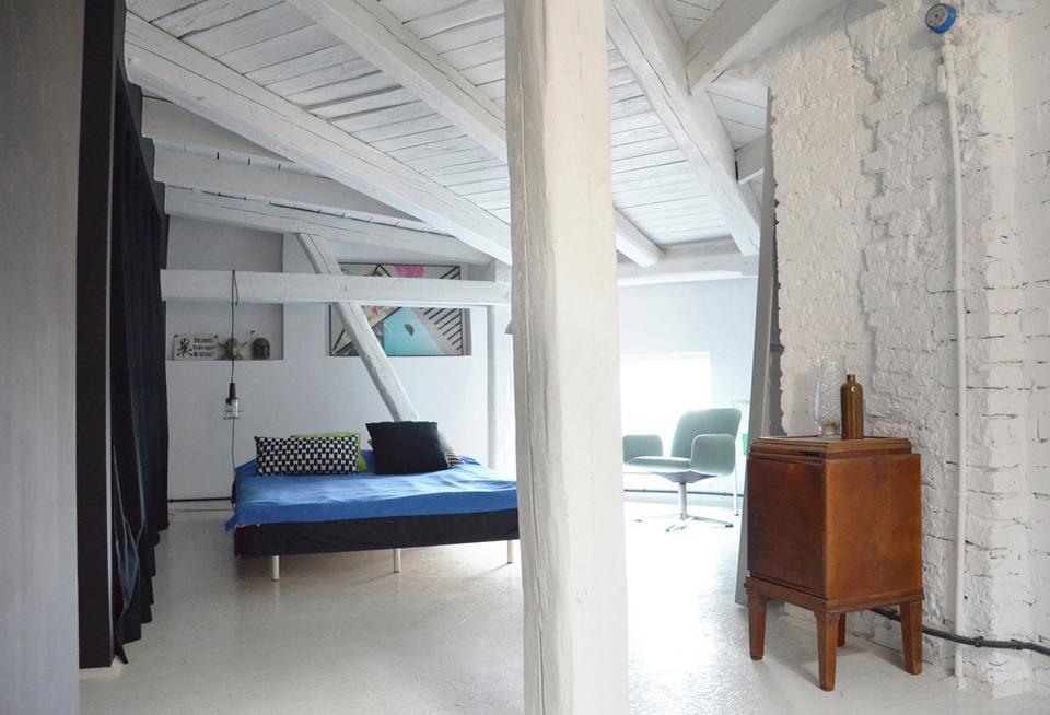 Sypialnia z łóżkiem wykonanym przez Grzegorza. Za czarną zasłoną kryje się szafa.