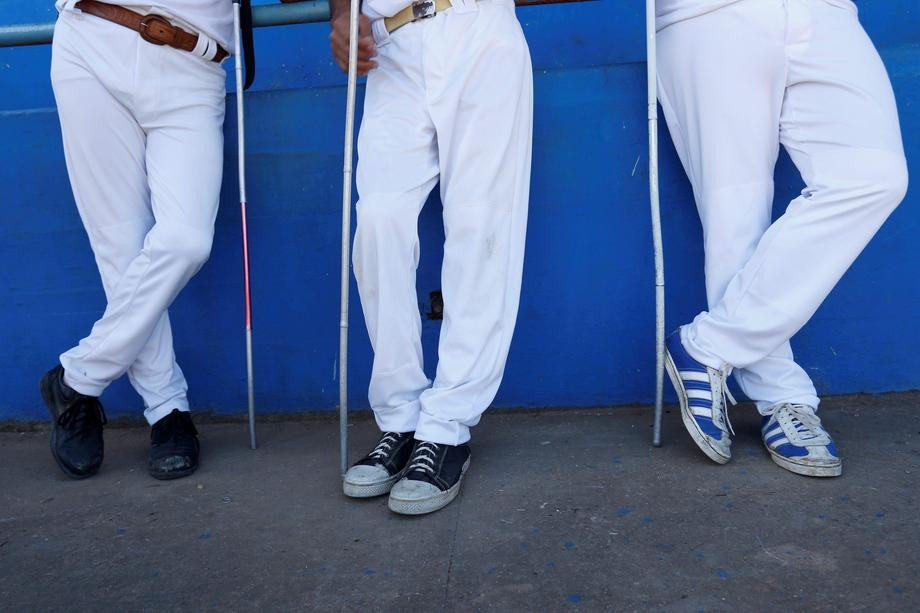 The visually impaired wait for a baseball lesson to begin at the Changa Medero stadium, in Havana