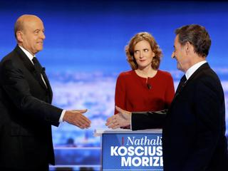 French politicians Alain Juppe and Nicolas Sarkozy shake hands as Nathalie Kosciusko-Morizet looks