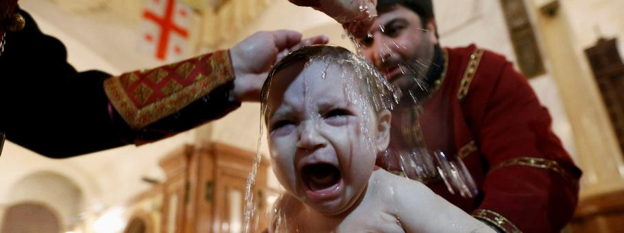 Baby is baptised during mass baptism ceremony on Orthodox Epiphany Day at Holy Trinity Cathedral in