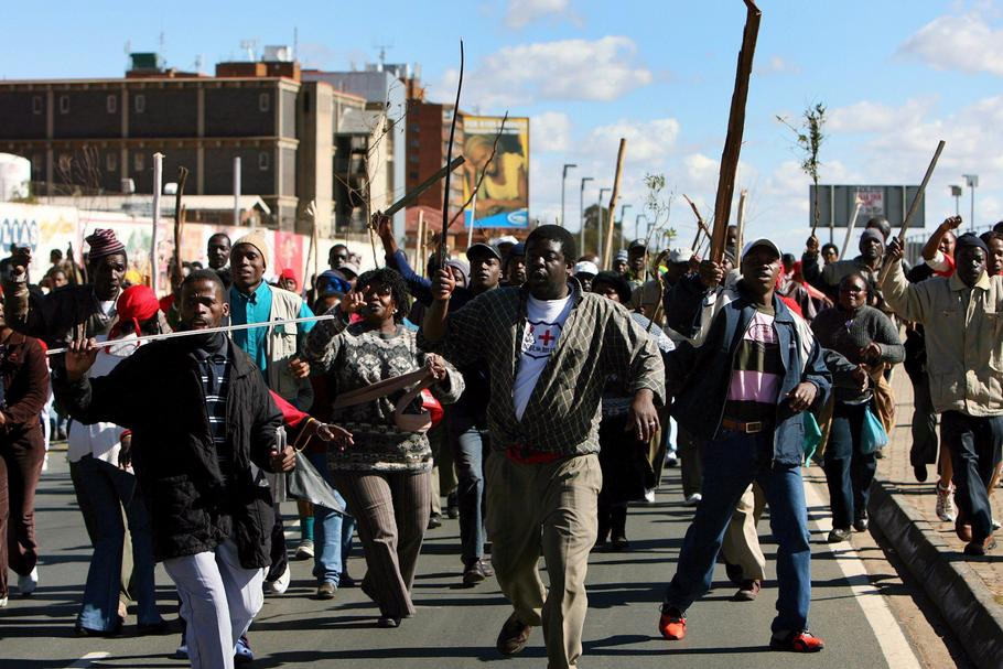 Striking public servants run through the streets outside the Chris Hani Baragwanath Hospital in Soweto near Johannesburg, South Africa