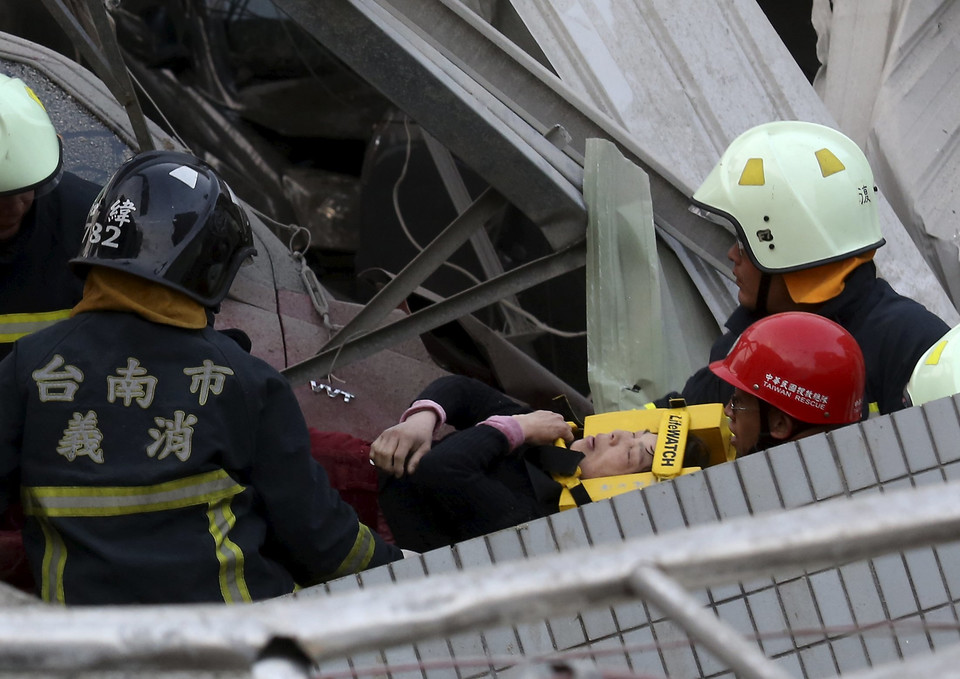 Rescue personnel help a victim at the site where a 17-storey apartment building collapsed, after an earthquake in Tainan