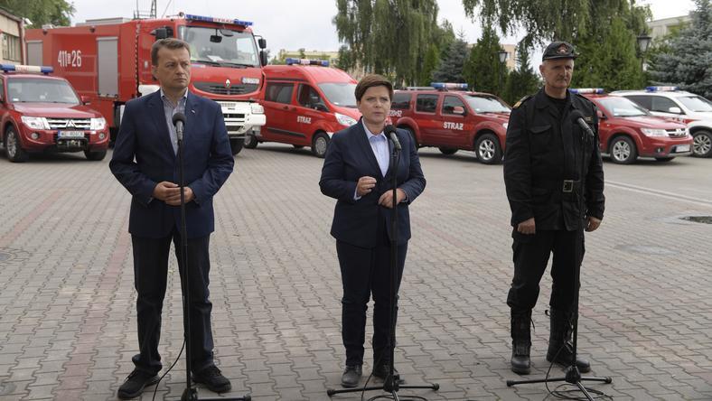 Premier Beata Szydło (C), komendant główny Straży Pożarnej Leszek Suski (P) i szef MSWiA Mariusz Błaszczak (L)