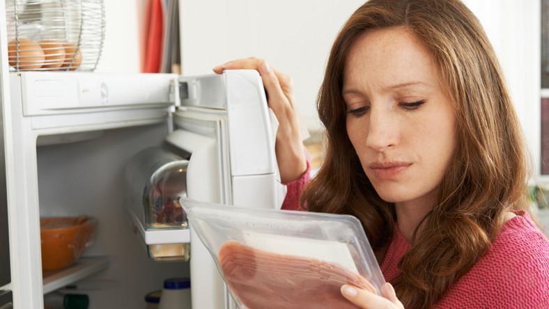 Kobieta wyjmuje z lodówki jedzenie i ogląda je