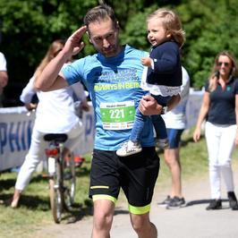 Piotr Kraśko biegnący z córką na ramieniu i Kinga Rusin we wzorzystej sukni, czyli Maraton Mazury