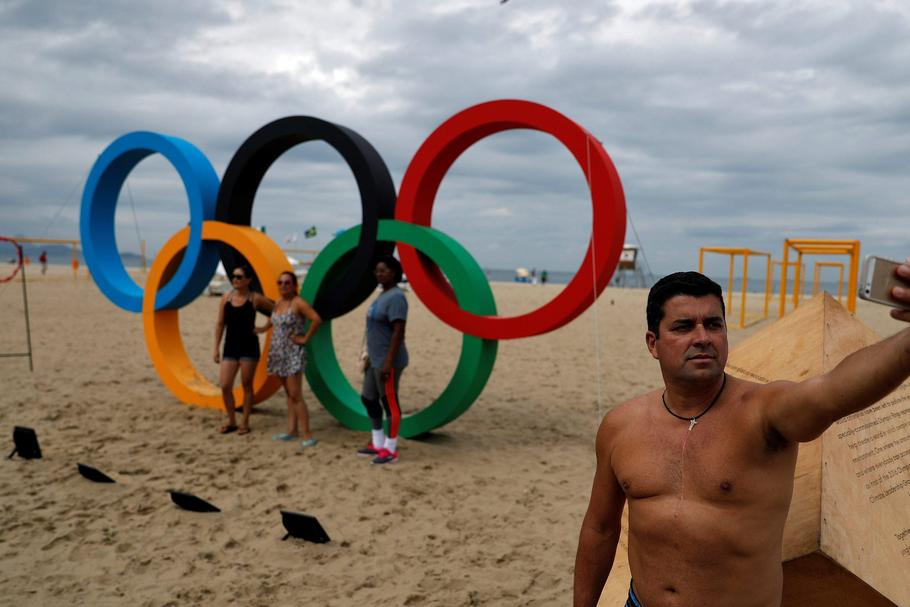 Man takes a selfie in front of the Olympic Rings, displayed at the Copacabana beach ahead of the 201