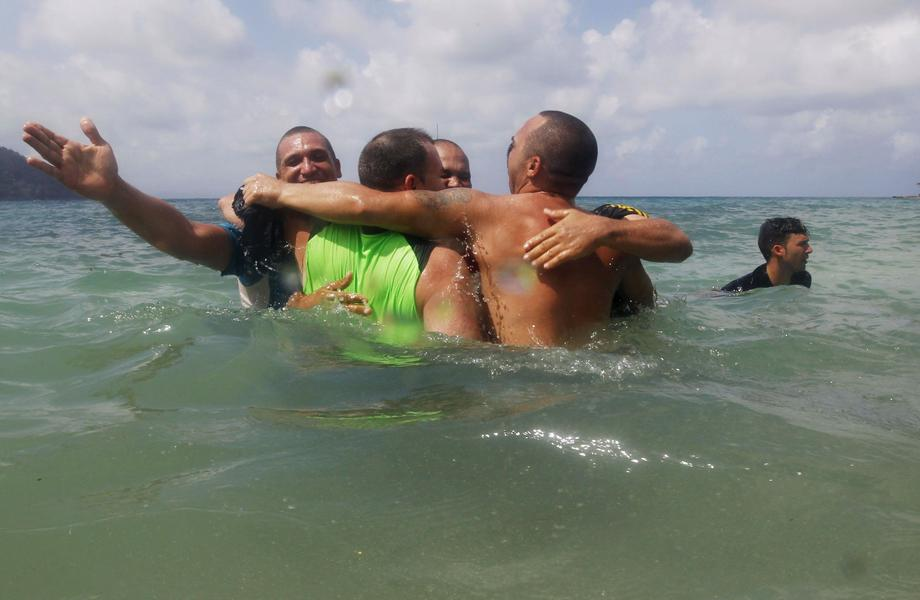 A group of Cuban migrants celebrate in the water upon arriving in a town after they crossed the bord