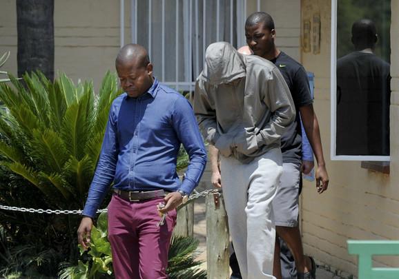 Trenutak kad Oskar Pistorijus (sa kapuljačom) napušta policijsku stanicu u Pretoriji