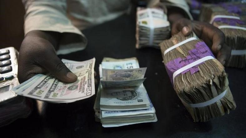 A trader changes dollars with naira at a currency exchange store in Lagos February 12, 2015.   REUTERS/Joe Penney